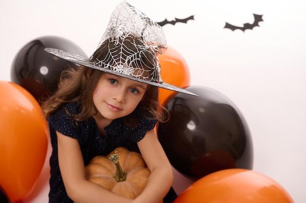 Portret van een mooi klein meisje met een tovenaarshoed, gekleed in een donker heksencarnavalkostuum, knuffelt een pompoen in haar hand, zit op een witte achtergrond met kleurrijke zwartoranje ballonnen en vleermuizen