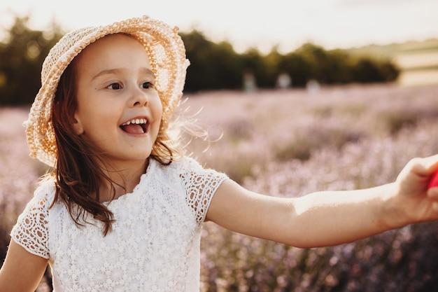 Portret van een mooi klein meisje met hoed wegkijken lachend tijdens het spelen in een veld van bloemen bij de zonsondergang.