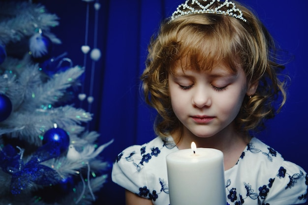 Portret van een mooi klein meisje met kaarsen op de achtergrond van de kerstboom