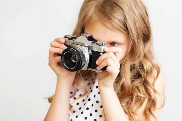 Portret van een mooi klein meisje met oude slr-filmcamera tegen een witte achtergrond
