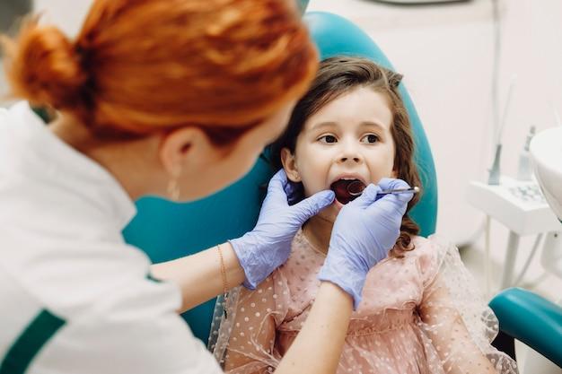 Portret van een mooi klein meisje, zittend in een stoel stomatologie met tandenonderzoek door een pediatrische stomatologist.