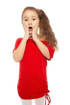 Portret van een mooi klein verrast meisje in rode die kleding op wit wordt geïsoleerd