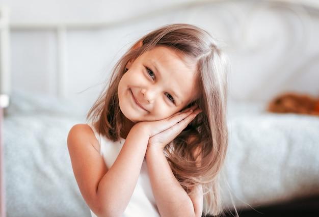 Portret van een mooi lachend meisje in een lichte kamer. detailopname. een blik op de camera