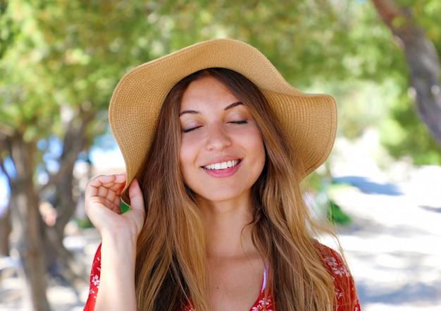 Portret van een mooi lachend meisje met gesloten ogen buitenshuis dragen van een hoed en een rode jurk close-up