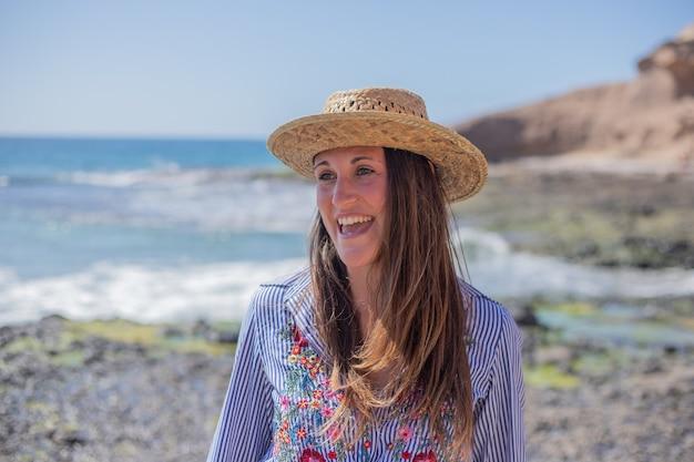 Portret van een mooi lachend meisje op het strand, gekleed in een bloemrijk shirt en een zomerhoed.