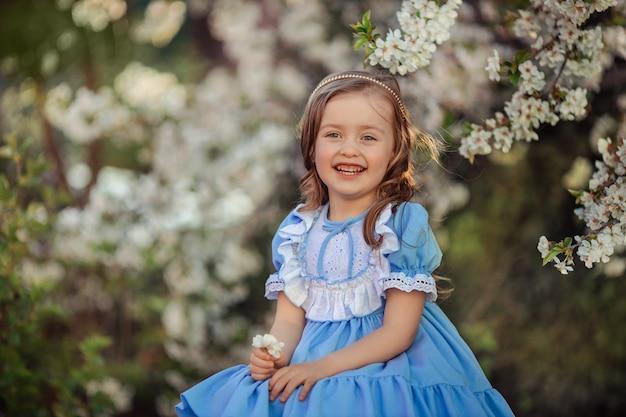 Portret van een mooi lachend prinsesmeisje in een blauwe jurk voor een wandeling in een bloeiende lentetuin