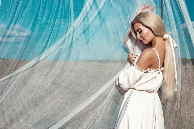Portret van een mooi meisje, blond met lang haar in een veld, op een achtergrond van witte transparante stof