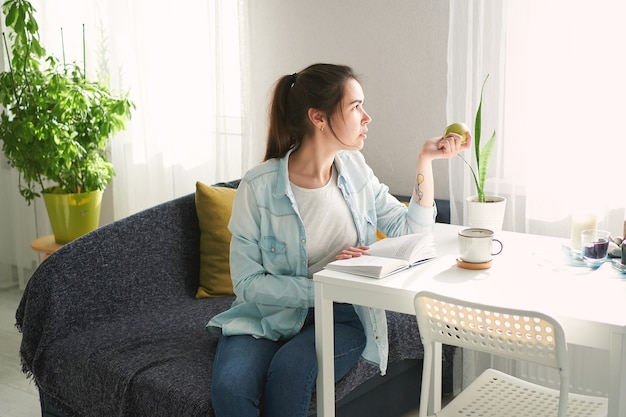 Portret van een mooi meisje dat aan tafel zit, een boek leest en een appel eet
