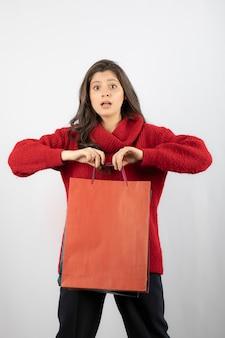 Portret van een mooi meisje dat boodschappentassen vasthoudt en naar de camera kijkt