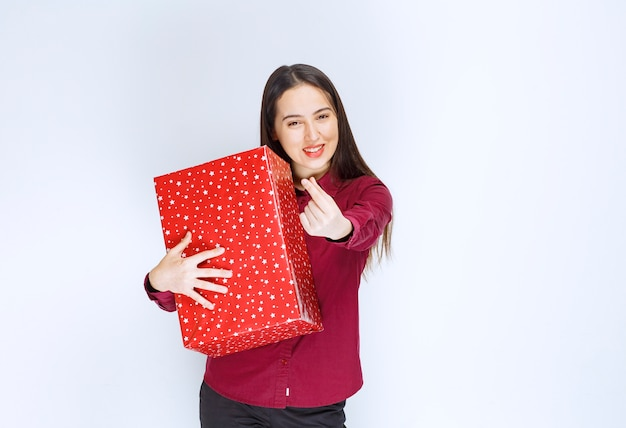 Portret van een mooi meisje dat de huidige doos over een witte muur houdt.