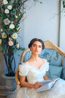 Portret van een mooi meisje dat een boek leest op een sofa in een mooie jurk