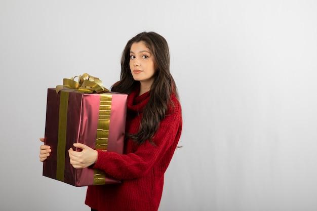Portret van een mooi meisje dat een geschenkdoos vasthoudt en naar een camera kijkt die over een witte muur wordt geïsoleerd.