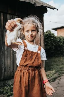 Portret van een mooi meisje dat een kleine gele kip in haar handen houdt
