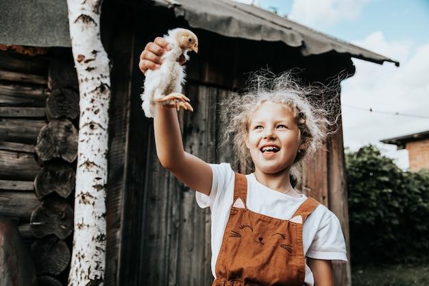 Portret van een mooi meisje dat een kleine kip in haar handen houdt