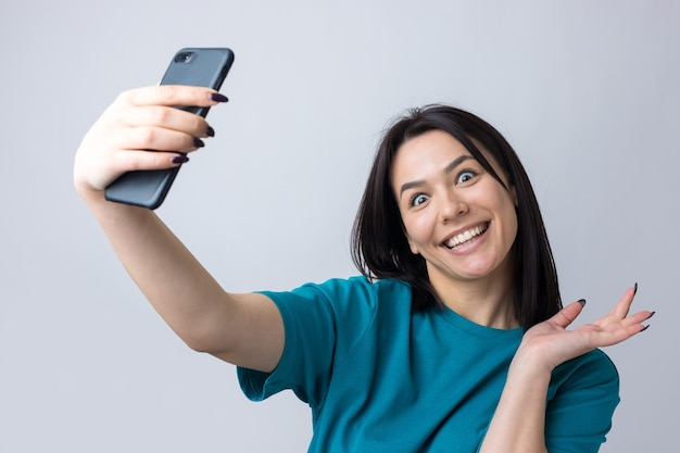 Portret van een mooi meisje dat een selfie neemt die over grijze achtergrond wordt geïsoleerd