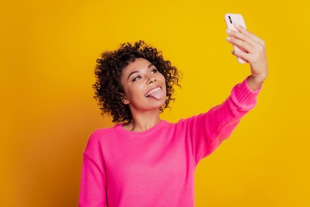 Portret van een mooi meisje dat een telefoon vasthoudt en een selfie toont met een tong