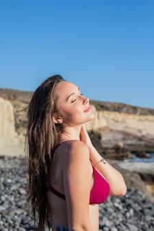 Portret van een mooi meisje dat geniet van de zon met haar ogen dicht op het strand concept van zorgeloos en vrijheid
