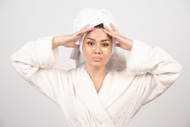 Portret van een mooi meisje dat hydrogelflarden onder de ogen draagt.