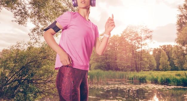 Portret van een mooi meisje dat in een zonnig park loopt in een koptelefoon met een smartphone. muziek apps-concept. gemengde media