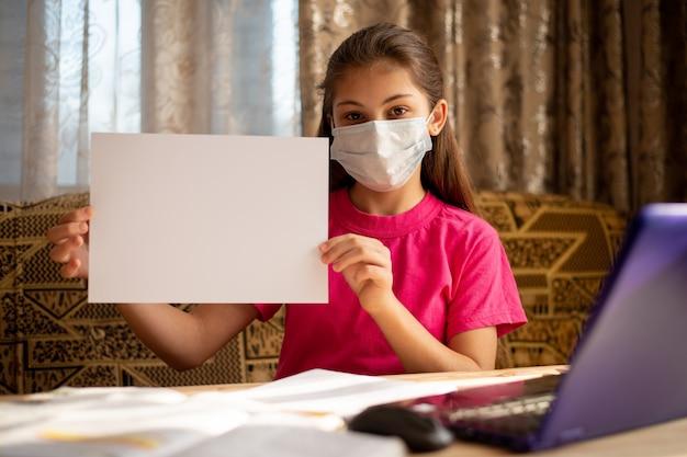 Portret van een mooi meisje dat in masker witboek voor inschrijving houdt, exemplaarruimte. concept van coronavirus quarantaine, afstandsonderwijs