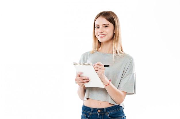 Portret van een mooi meisje dat nota's in een blocnote maakt