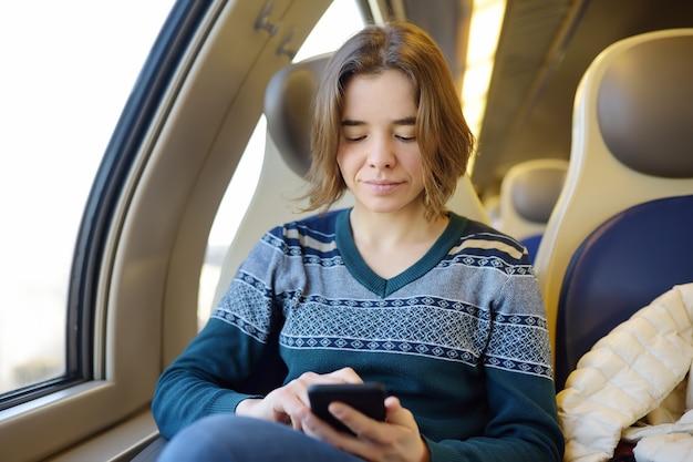 Portret van een mooi meisje dat op de telefoon in een treinauto communiceert. mobiele communicatie - het plezier van communicatie overal
