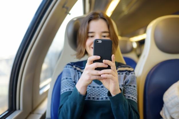 Portret van een mooi meisje dat op de telefoon in een treinauto communiceert.