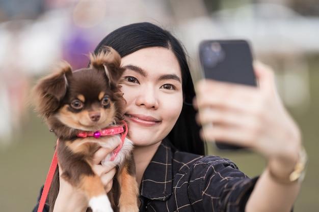 Portret van een mooi meisje dat speelt met haar mooie puppy buiten in het openbare park. kleine hond met eigenaar brengt een dag door in het park om te spelen en plezier te maken. huisdier liefde stockafbeelding