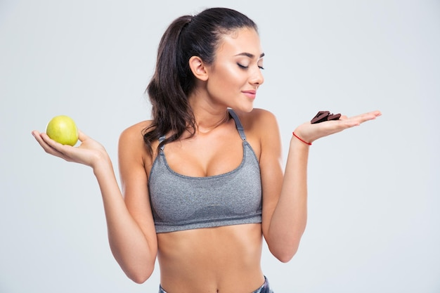 Portret van een mooi meisje dat tussen appel of chocolade kiest die op een witte muur wordt geïsoleerd