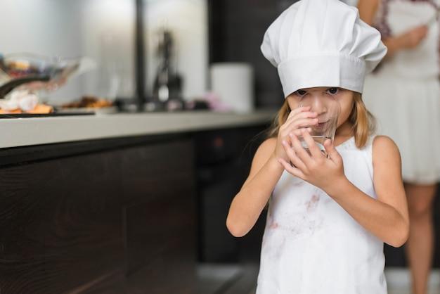 Portret van een mooi meisje die het drinkwater van de chef-kokhoed in glas dragen