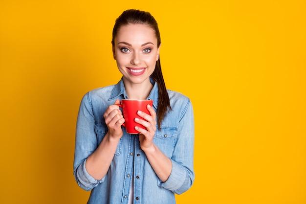 Portret van een mooi meisje heeft vrije tijd, houdt hete latte-beker vast en draagt mooie kleding die is geïsoleerd over een achtergrond met levendige kleuren