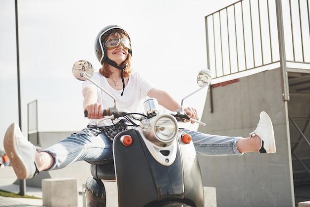 Portret van een mooi meisje hipster zittend op een zwarte retro scooter