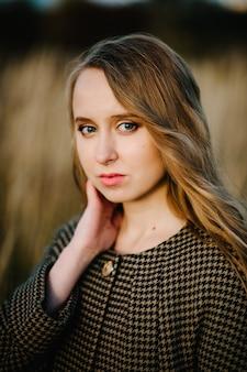 Portret van een mooi meisje in de herfst tegen het veld op de natuur.