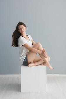 Portret van een mooi meisje in de studio op een grijze achtergrond