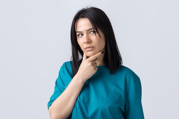 Portret van een mooi meisje in een blauw t-shirt, kijkt opzij met peinzende uitdrukking, overweegt een plan voor verdere actie.