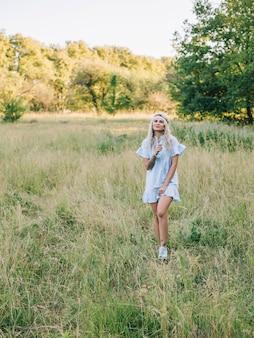 Portret van een mooi meisje in een blauwe jurk in een veld bij zonsondergang in de zomer.