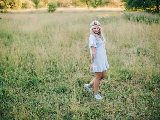 Portret van een mooi meisje in een blauwe jurk in een veld