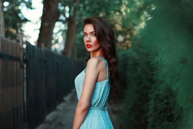 Portret van een mooi meisje in een blauwe jurk op een wandeling