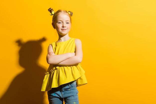 Portret van een mooi meisje in een gele blouse en spijkerbroek.