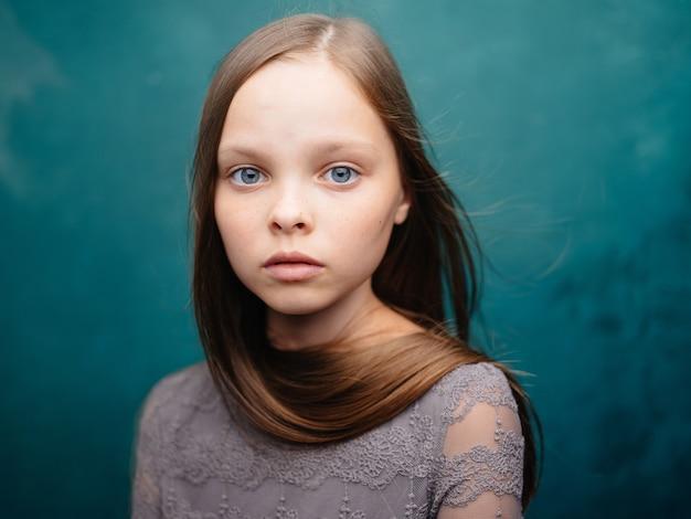 Portret van een mooi meisje in een grijze jurk en blonde haren op een turkooizen achtergrond. hoge kwaliteit foto