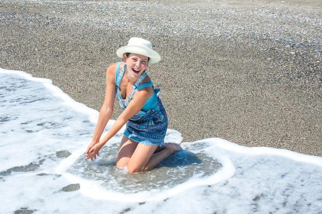 Portret van een mooi meisje in een hoed die gelukkig glimlacht en in de golven op het strand stelt.