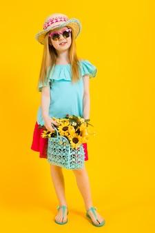 Portret van een mooi meisje in een hoed, zonnebril, zomerjurk en sandalen.