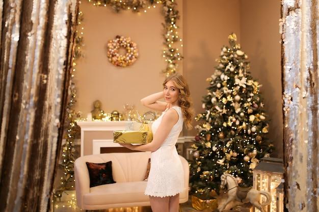 Portret van een mooi meisje in een jurk staat met geschenken in de buurt van de boom in een luxe interieur