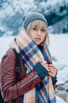 Portret van een mooi meisje in een muts en sjaal op een achtergrond van snowcappe een blik op de camera