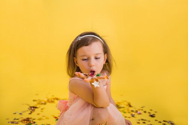 Portret van een mooi meisje in een roze gezwollen jurk waait confetti uit haar hand. verjaardagsfeest.