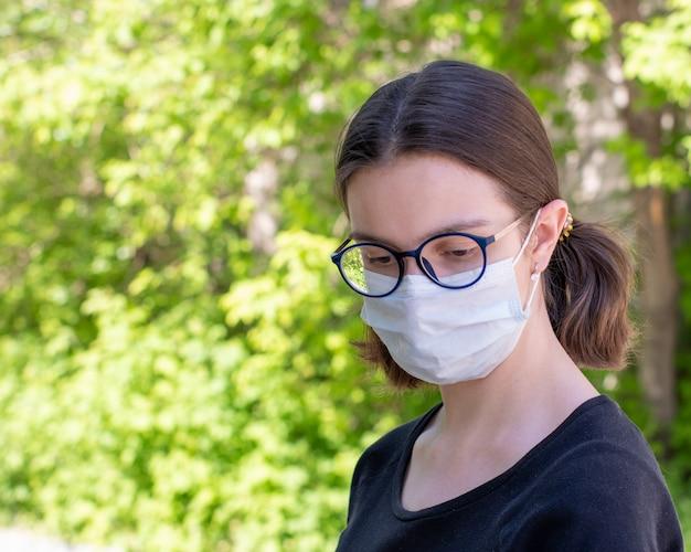 Portret van een mooi meisje in een wegwerp medisch masker op een onscherpe achtergrond van groen gebladerte