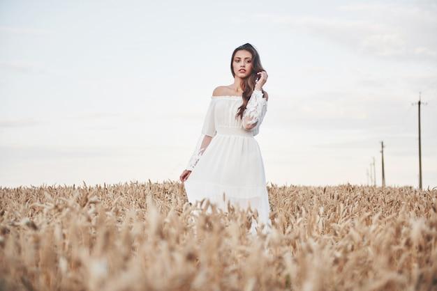 Portret van een mooi meisje in een witte jurk op het gebied van tarwe