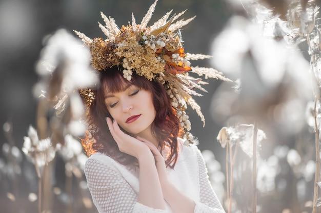 Portret van een mooi meisje in een witte vintage jurk en herfstkrans van gedroogde bloemen op het hoofd in het midden van luchtige en pluizige planten