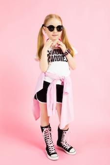 Portret van een mooi meisje in korte broek, een t-shirt en hoge sneakers.