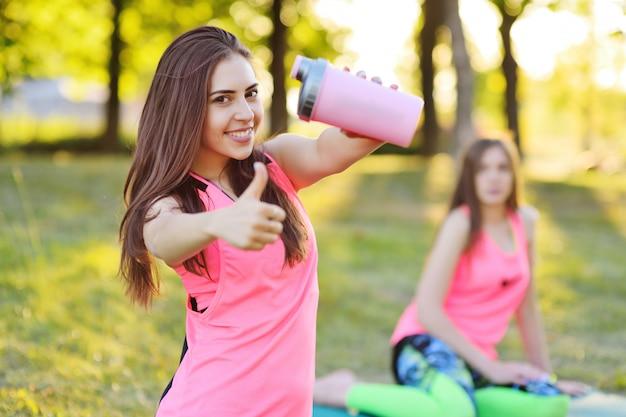 Portret van een mooi meisje in roze sportkleren, dat een fles water of een eiwitcocktail vasthoudt.